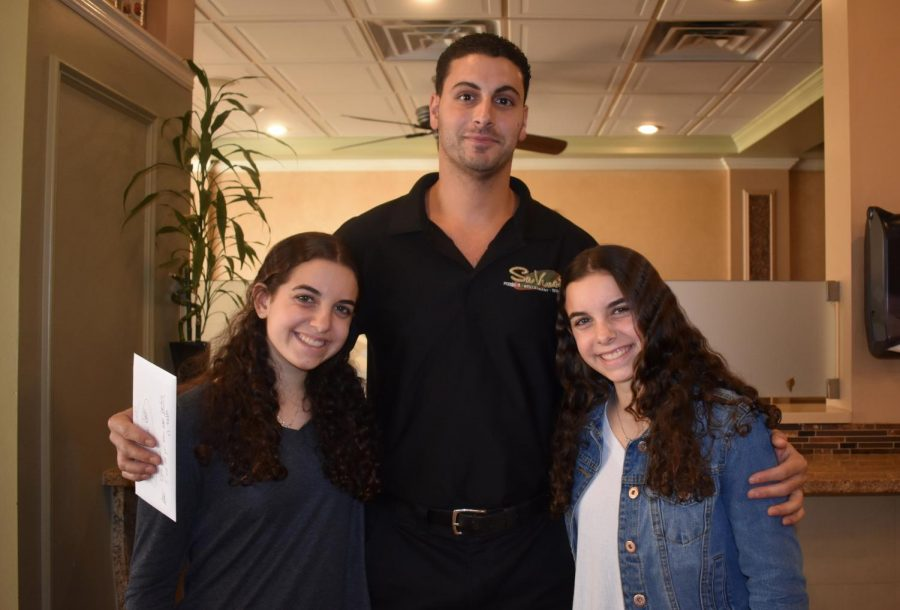 Sophie and Emma Ward accept a check on behalf of the SCOPE club from Michael Biancaniello, proprietor  of SaVinos